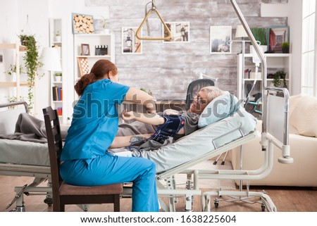 Young nurse checking the blood pressure of sick old woman in nursing home.