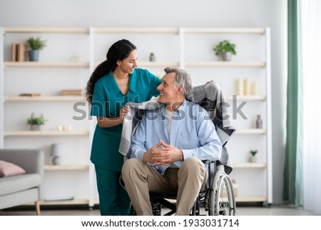 Young nurse covering disabled elderly man in wheelchair with warm plaid at retirement home. Millennial caregiver assisting handicapped senior patient, taking care of older male indoors