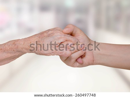Young nurse holding old patient hand in hospital