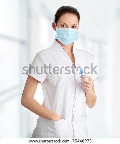 Young nurse in mask with syringe, isolated on white background - stock photo