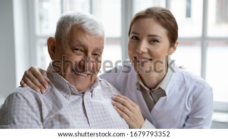Young nurse in white coat hugging old 80s man smiling looking at camera. Portrait of satisfied patient and his caregiver. Medical care of older generation people, geriatrics medicine, nursing concept