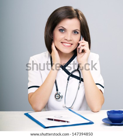 Young nurse sitting at the table. Talking on a mobile phone. Isolated on a gray background