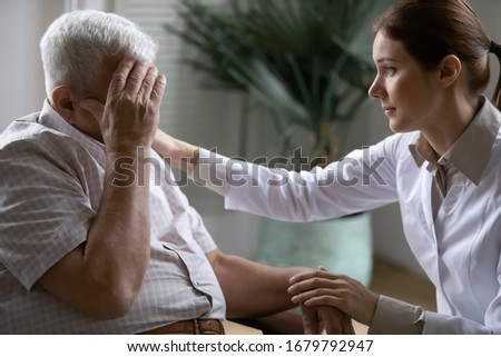 Young nurse spend time with old man, shares his pain, express empathy caring about 80s patient provide psychological support listens his life health complaints in diseases, relieves loneliness concept