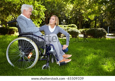 Young nurse talking to woman in wheelchair in park