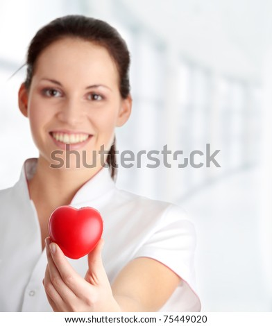 Young nurse with heart in her hand, isolated on white background
