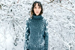 Young odd beautiful adorable lovely girl in knitted sweater portrait outdoor in cold winter forest. Fashionable model in trendy glasses with snow covered hair bang freezing. Nice looking woman face