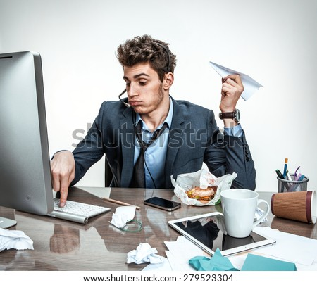 Young office man with paper plane in his hand typing on a computer keyboard / modern office man at working place, sloth and laziness concept