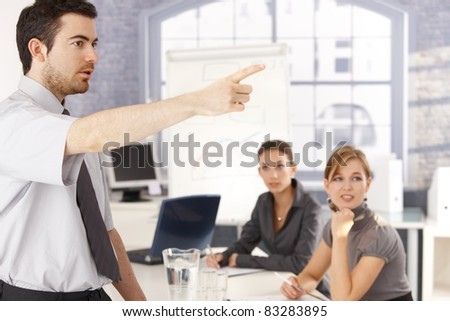 Young office worker leading business training, pointing, colleagues listening.?