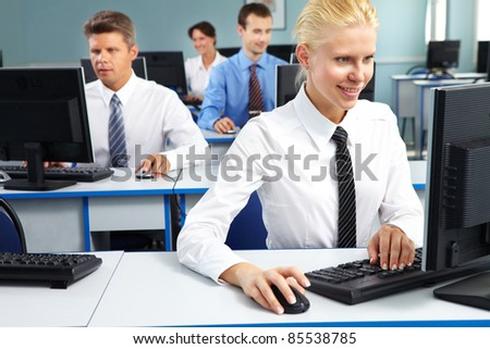 Young office worker sitting at computer and working among her colleagues