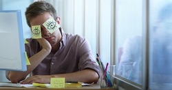 young office worker taking a break,He jokes with a sticky notes stuck in the eyes to sleep