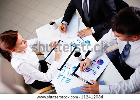Young office workers discussing papers at meeting