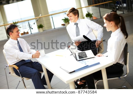 Young office workers talking with each other during break