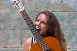 Young optimistic curly hippie girl holding and biting guitar. Music concept. Fun happy woman with guitar on stone wall background.
