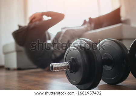 Young ordinary man go in for sport at home. Cut view of a beginner or freshman in workout activity at his apartment. dumbbells on pictures lying on floor. Trying to get better shape Foto d'archivio ©