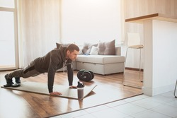 Young ordinary man go in for sport at home. Full size picture of regular ordinary guy stand in plank position alone in room. Beginner try to do his best and exercise. Hardworking real person