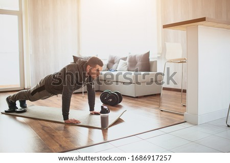 Young ordinary man go in for sport at home. Full size picture of regular ordinary guy stand in plank position alone in room. Beginner try to do his best and exercise. Hardworking real person Foto d'archivio ©