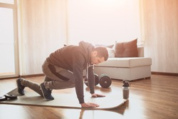 Young ordinary man go in for sport at home. Picture of real ordinary man doing abs exercising by running on one place with legs. Worksout freshman warming up body. Stretching alone in sunny apartment