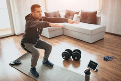 Young ordinary man go in for sport at home. Real picture of egular guy doing squats with stretch hands forward. Beginner or amateur has workout in apartment. Sport equipment on floor