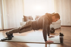 Young ordinary man go in for sport at home. Regular norman guy without big muscles stand in full plank position. Freshman started to work on his body shape. Real man exercising to get better