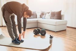 Young ordinary man go in for sport at home. Stand on mat and stretch down to toes. Ordinary guy warming out body before exercise. Working out alone in middle of room. Sport ewuipment on floor