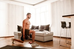 Young ordinary man go in for sport at home. View of hardwoking t-shirtless guy sportsman gets up and crouches on floor and hold dumbbells in hand. Ready to start workout. Ordinary man work on