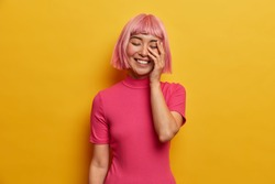 Young overjoyed woman laughs happily, makes face palm, closes eues from laughter, shows white teeth, has pink hair, grins over yellow background, spends free time with comic friend who tells jokes