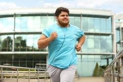 Young overweight man running outdoors. Fitness lifestyle