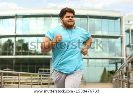 Young overweight man running outdoors. Fitness lifestyle Photo stock ©