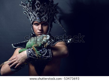 Young pagan priest in ritual suit with green iguana in his hands. Photo.