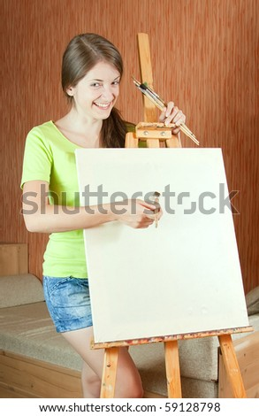 Young painter near easel in living room