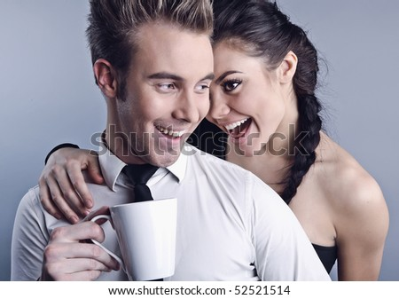 Young pair acquaintance. He holds a mug in his hands, she shows liking. Photo.