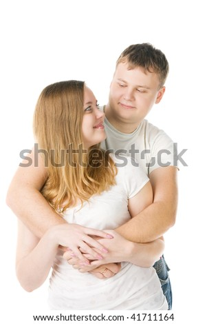 young pair in white T-shirts, the man embraces the girl, isolated on white