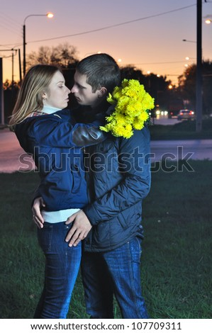 young pair kisses in the evening near the road
