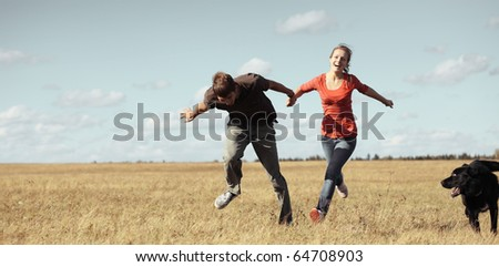 Young pair running on meadow with a dog