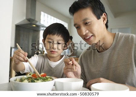 Young parent sitting at table, watching son trying to use chopsticks