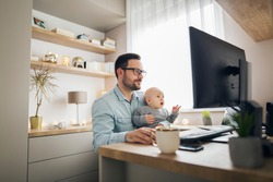 Young parent working from home while holding his baby boy on his lap while they both watch to the screen.