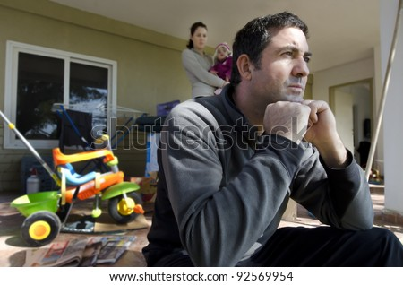 Young parents and their daughter outside their home. Concept photo illustrating divorce, homelessness, eviction, unemployment, financial, marriage problem or family issues.