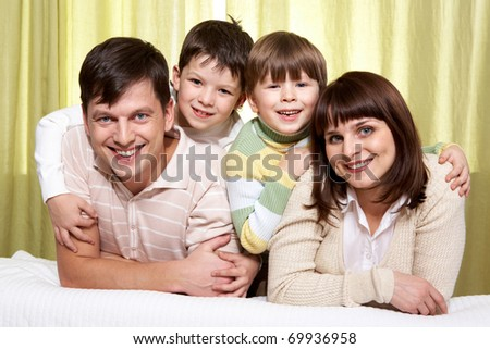 Young parents ant two sons embracing them, looking at camera and smiling