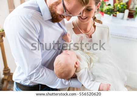 Young parents at the church with their baby wearing a christening gown