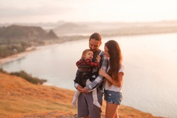 Young parents cares baby in ergo backpack on a stone cliff at ocean, sunset tome