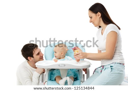 Young parents feed  baby on a white background. Happy family.