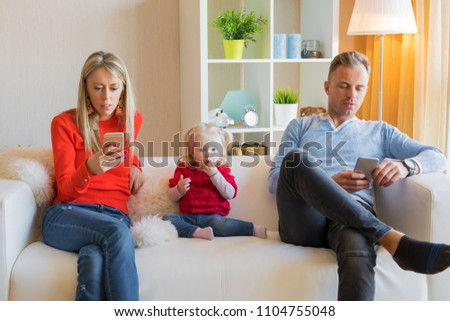 Young parents ignore their kid and looking at their mobile phones #1104755048