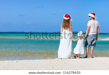 Young parents in Santa hats and their little daughter on a tropical beach