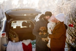 Young parents of the family are holding a little daughter and a dog on the background of Christmas decorations in the trunk of an SUV