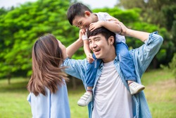 Young parents play with kid and let him sit on father shoulder
