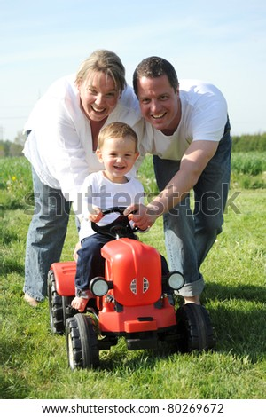 Young parents playing with son sitting on red tractor