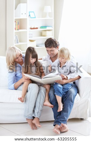 Young parents read the book to children at home