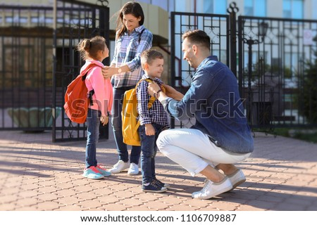 Young parents saying goodbye to their little children near school #1106709887