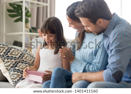 Young parents sit on couch make birthday surprise to excited cute preschooler daughter, happy little girl child amazed by gift box present by mom and dad, mother and father congratulate small kid