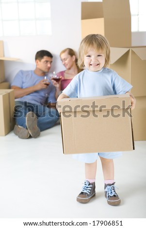 Young parents sitting beside cardboard boxes and drinking wine. Theirs daughter standing in frond and holding box. She's looking at camera.